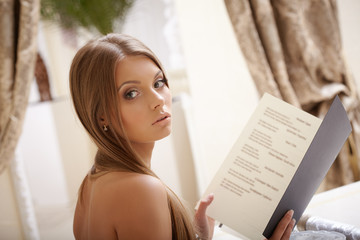 Image of charming young lady reads menu