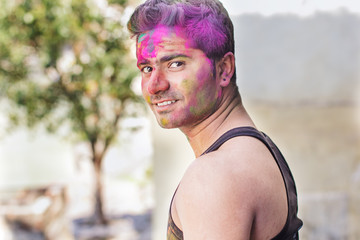 Portrait of Indian guy with colorful paint on face