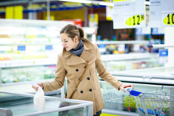pretty young woman buying groceries in a supermarket/mall/grocer
