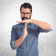 Young hipster man making time out gesture