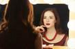 beautiful woman is applying makeup