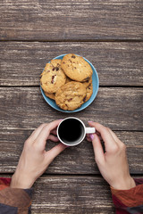 Female holding cup of coffee near cookies