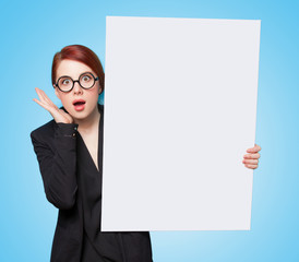 Surprised redhead women with white board