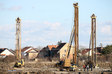 construction site with workers and three hydraulic drilling mach