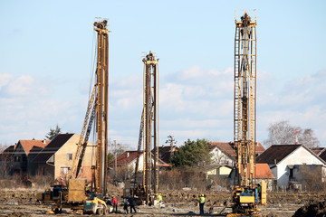 three hydraulic drilling machines and workers on construction si