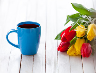 Cup of coffee and bouquet of tulips