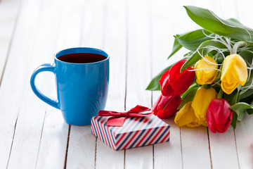 Cup and gift box with bouquet of tulips