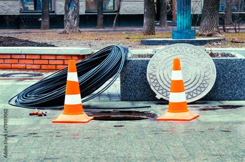 Leinwanddruck Bild Open manhole with few cables