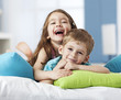 Portrait of two smiling siblings lying on cushions - 79889238
