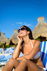 Happy woman relaxing on vacation at tropical resort beach