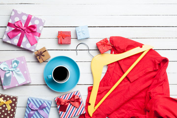 Cup of coffee and gifts with clothes