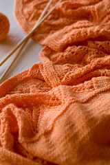 Bright orange plaid knitted, knitting needles and yarn balls