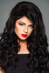 Beautiful brunette lady with makeup and fashion curly hairstyle