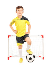 Junior soccer player standing in front of a small goal