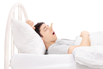Man sleeping with a clothespin on his nose