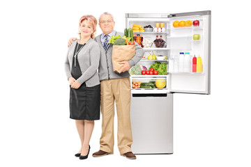 Mature couple holding groceries in front of a fridge