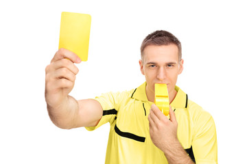 Referee showing yellow card and blowing huge whistle