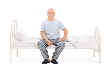 Senior man in pajamas sitting on a bed