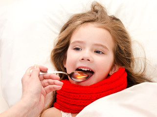 Little girl in bed taking medicine with spoon