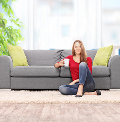 Woman drinking coffee seated by a sofa
