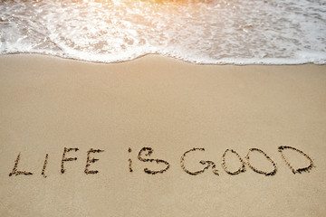 life in good written on sand beach - positive thinking concept