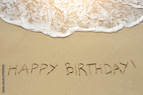 Deurstickers Water happy birthday written on sand beach