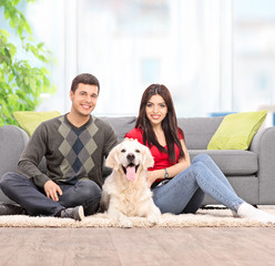 Couple sitting on the floor with a dog at home