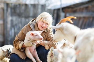 female farmer holding a small pig