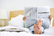man reading newspaper in bed - 79892298