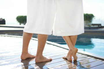 Legs of a couple in bathrobe at a poolside