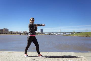 Chica joven haciendo ejercicio junto al rio