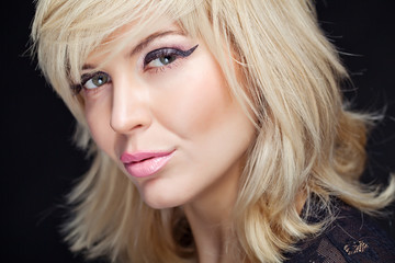 Portrait sexy blonde in studio, black background