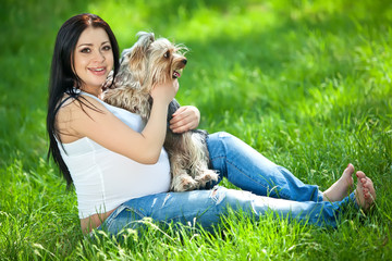 Pregnant woman are playing with dog on grass