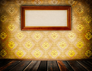 Wall with vintage floral wallpaper and old wooden frame.