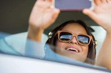 Smiling teenage girl taking selfie