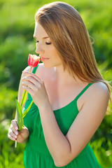 woman are enjoying the smell tulip in green field