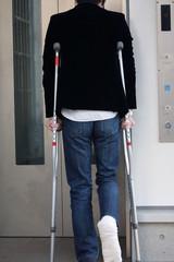 エレベーターを待つ松葉杖の男性