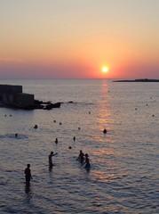Tutisti giocano a palla in acqua alla luce del tramonto