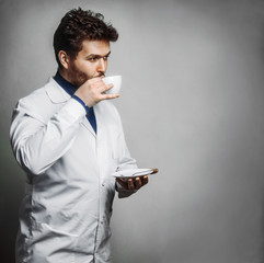 Young breaded doctor drink tea coffee