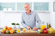 Mature man in the kitchen prepare fruits for breakfast. V