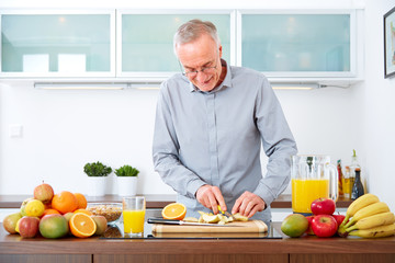 Mature man in the kitchen prepare fruits for breakfast. III