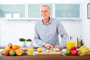 Mature man in the kitchen prepare fruits for breakfast. VI