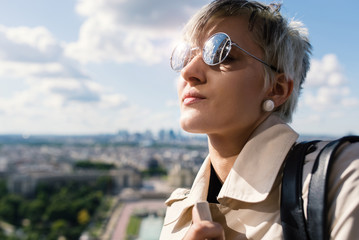 Young blonde woman portrait on top of the Eiffel Tower with Troc