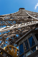 Detail of Eiffel Tower and elevator isolated against blue sky fr