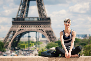Smiling young blonde woman portrait in front of the Eiffel Tower