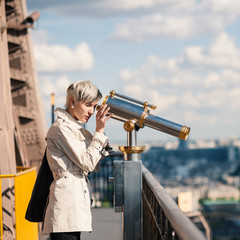 Young blonde woman looks through telescope on top of the Eiffel