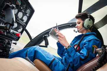 Young woman helicopter pilot reading map.