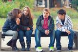 Teenage boys and girls having fun in the park on beautiful sprin