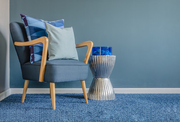 wooden chair with blue color pillow on carpet