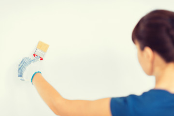 woman with paintbrush colouring the wall
